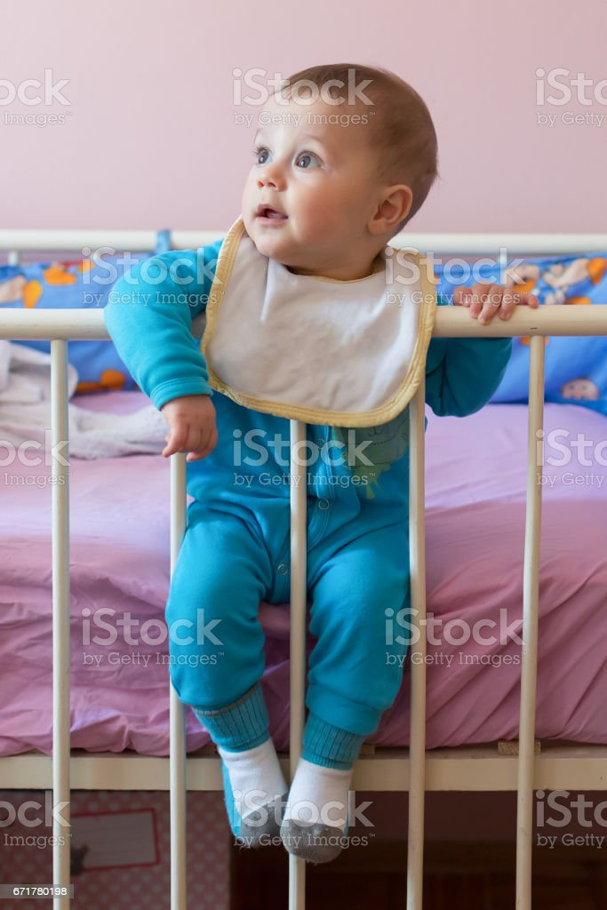 Cute happy baby sitting in crib stock photo