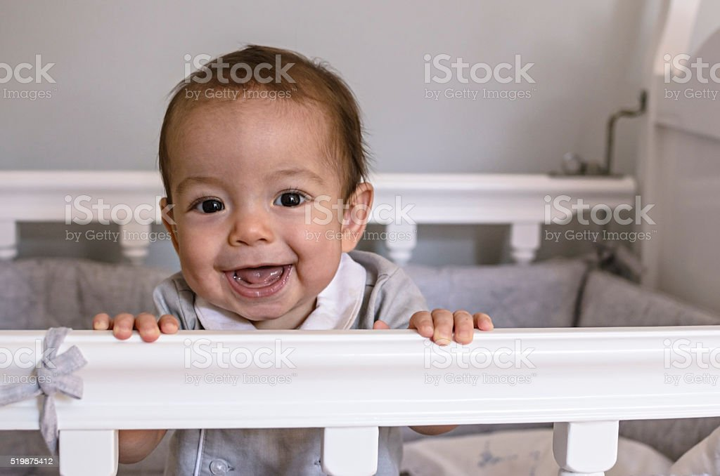 Cute happy baby smiling in crib stock photo
