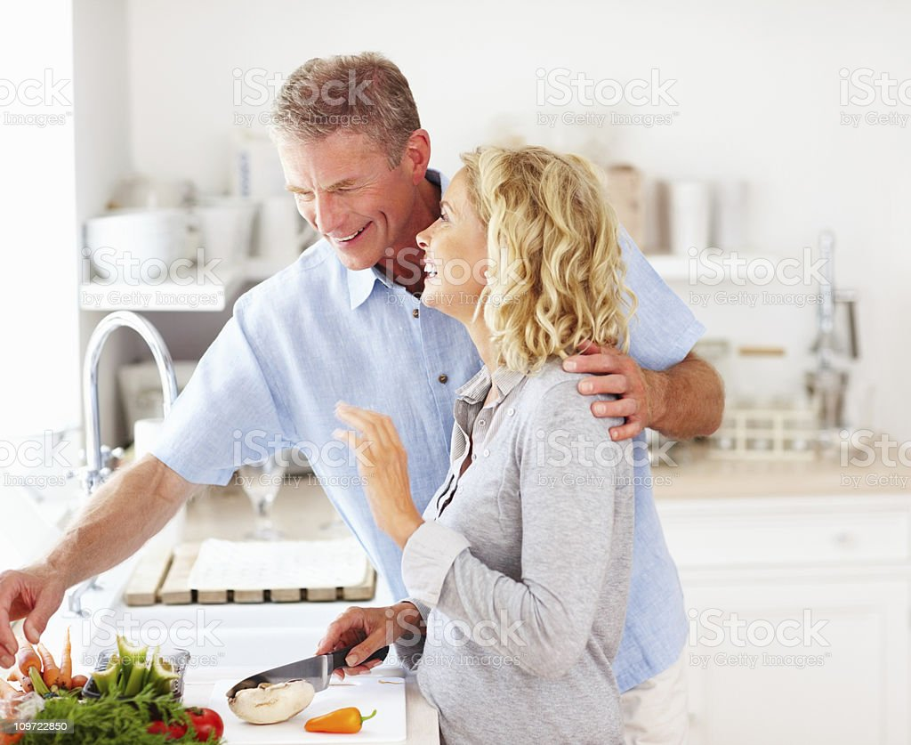 Cute happy mature couple preparing food in kitchen stock photo