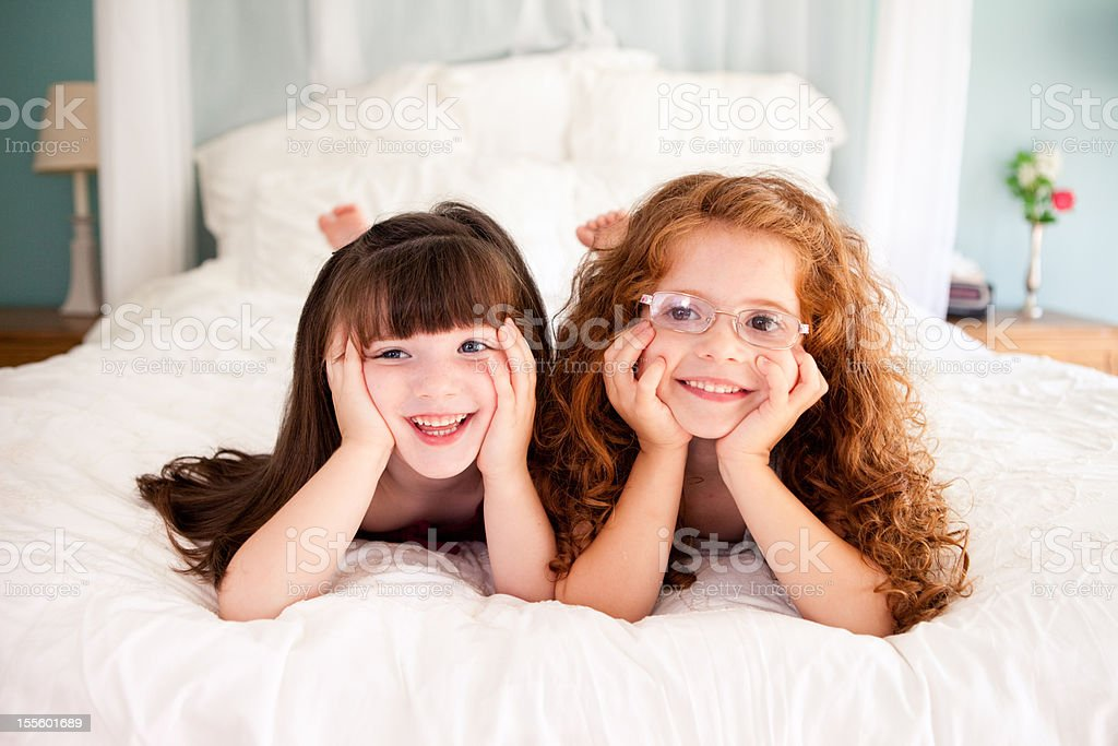 Cute, Happy Sisters Lying on Bed Together in Their Home royalty-free stock photo