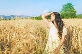 cute happy teenager standing on wheat field