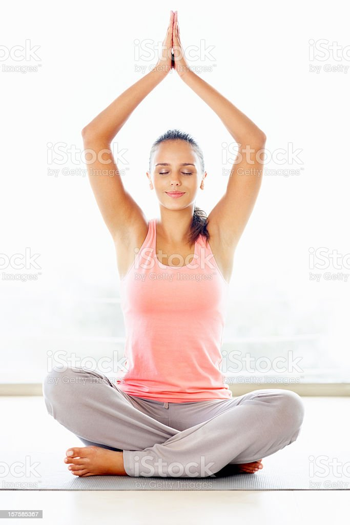 Cute happy woman meditating with hands joined over head stock photo