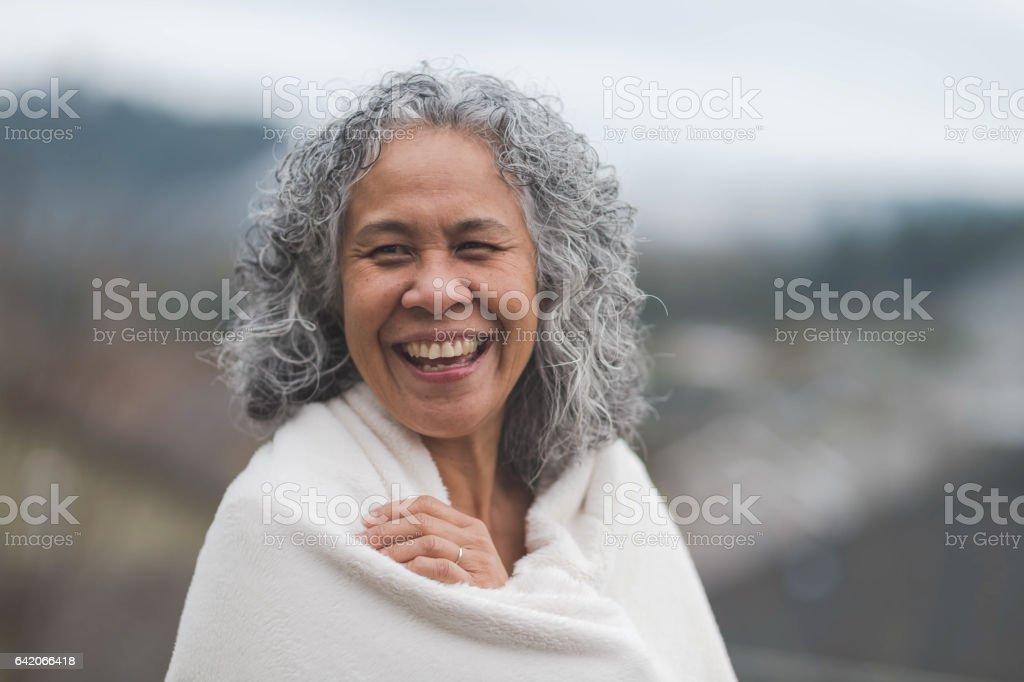 Cute Hawaiian woman in 50s outside smiling at camera joyfullyl stock photo