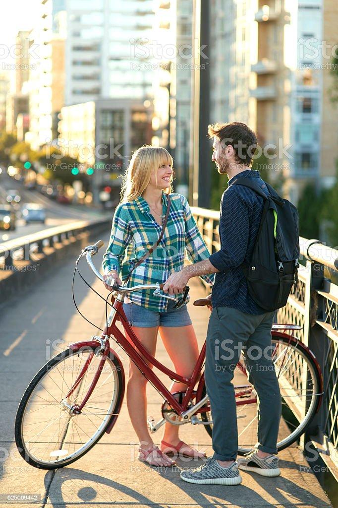 Cute heterosexual couple flirting while standing on a bridge stock photo