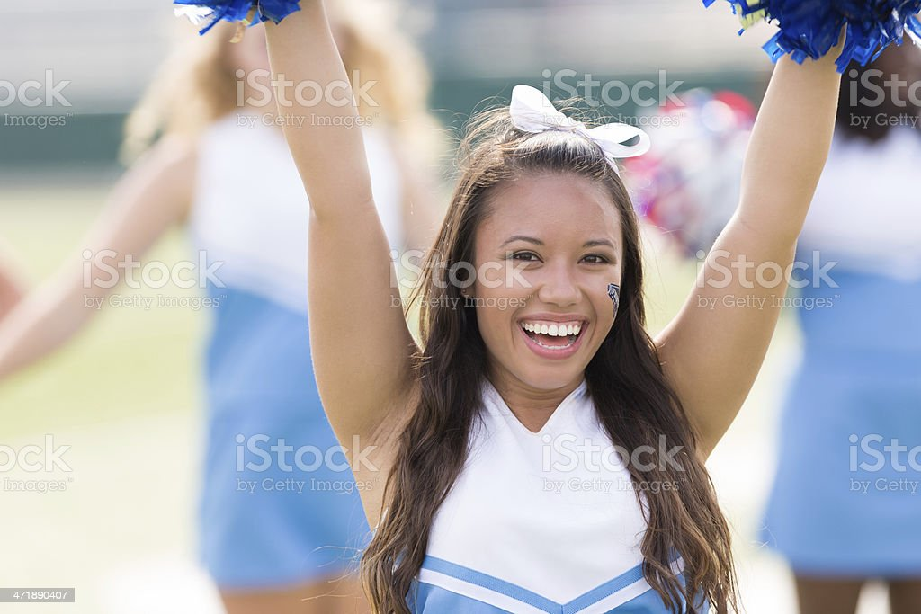 Cute high school cheerleader performing at football game royalty-free stock photo