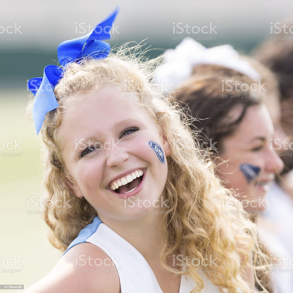 Cute high school cheerleader performing with squad at football game royalty-free stock photo