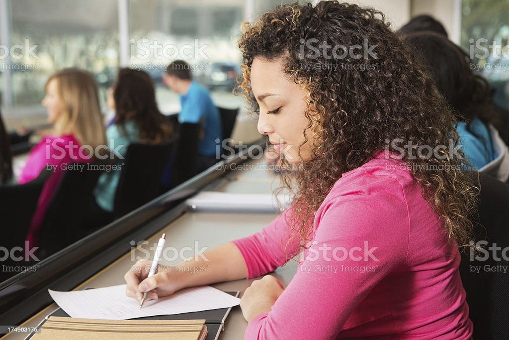 Cute high school or college girl taking notes in classroom royalty-free stock photo