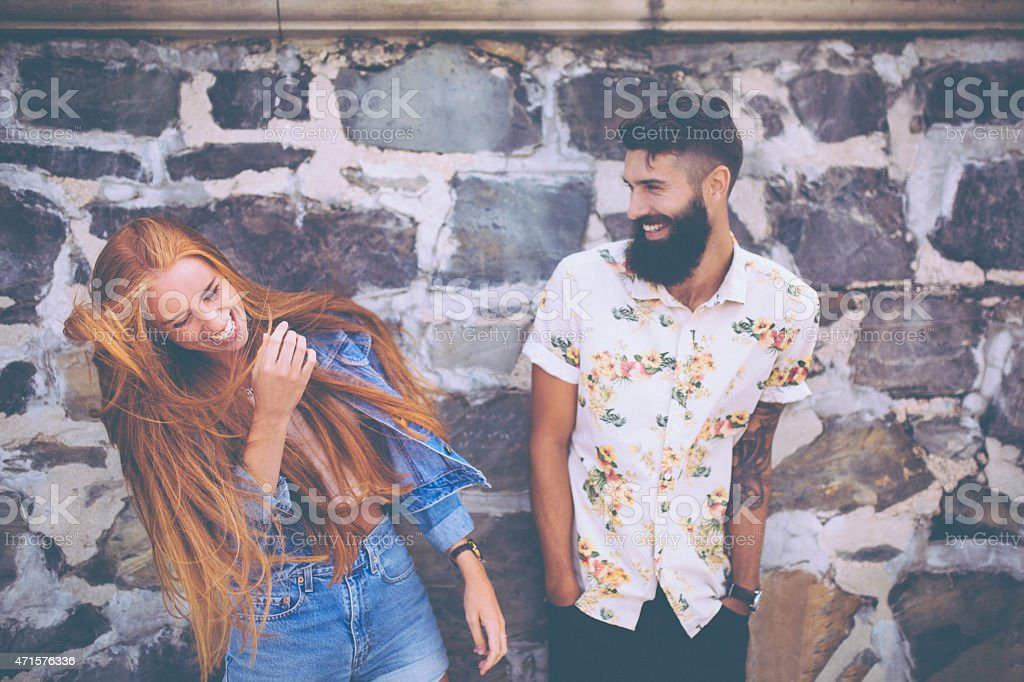 Cute hipster couple laughing in front of a stone wall stock photo