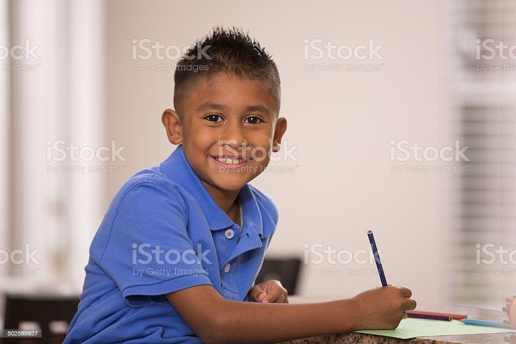 Cute Hispanic boy does homework in home kitchen. stock photo
