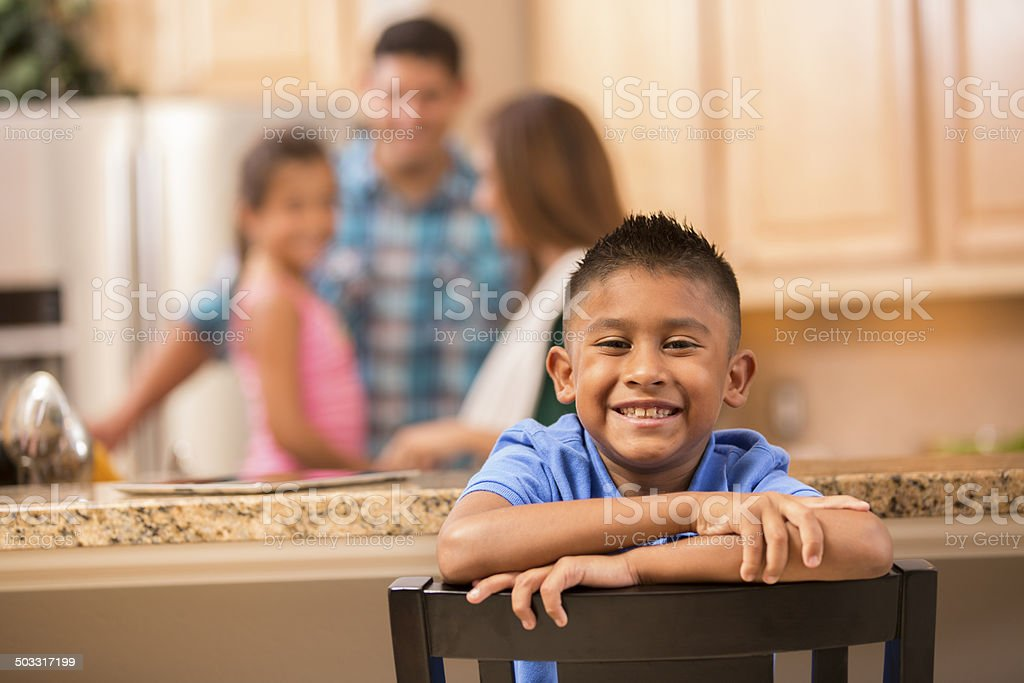 Cute Hispanic boy in home kitchen. Family background. Tablet countertop. stock photo
