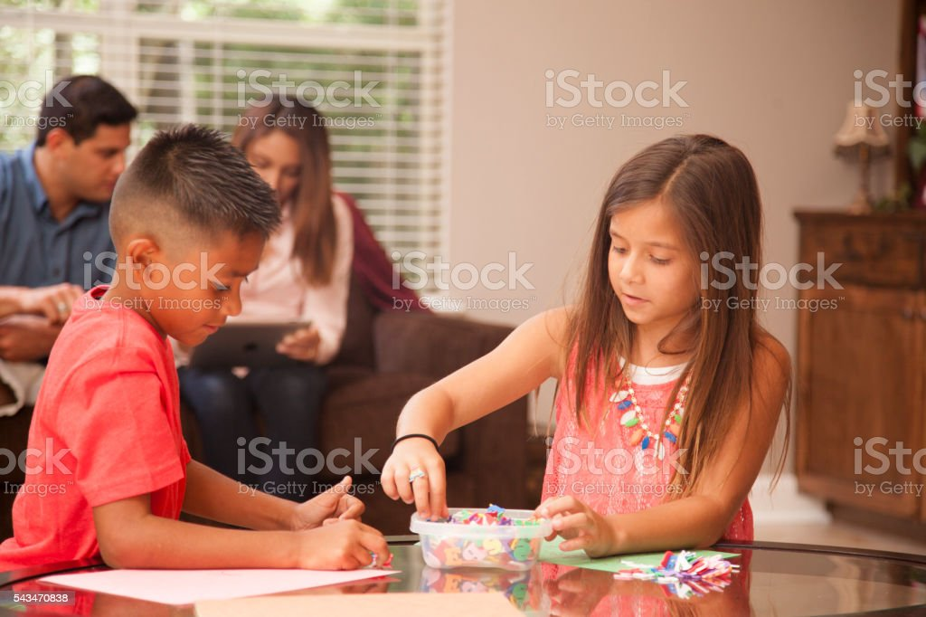 Cute Hispanic children do homework at home together. Family. stock photo