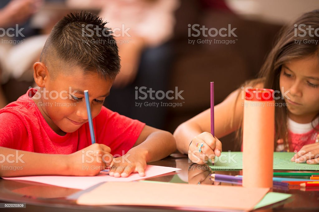 Cute Hispanic children do homework at home together. stock photo