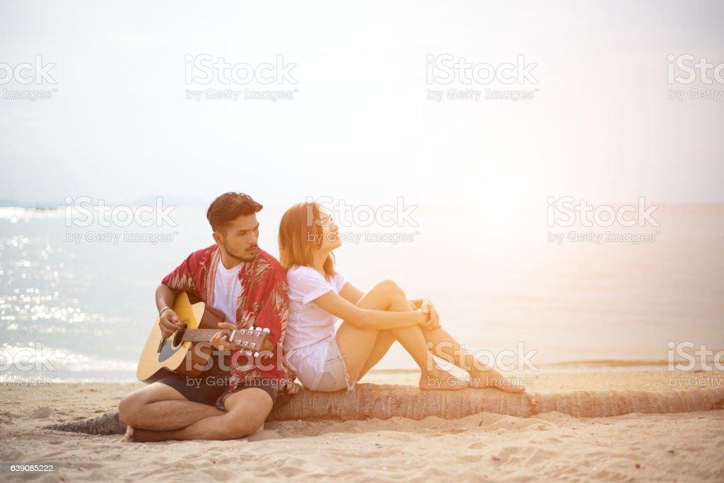 Cute hispanic couple playing guitar serenading stock photo