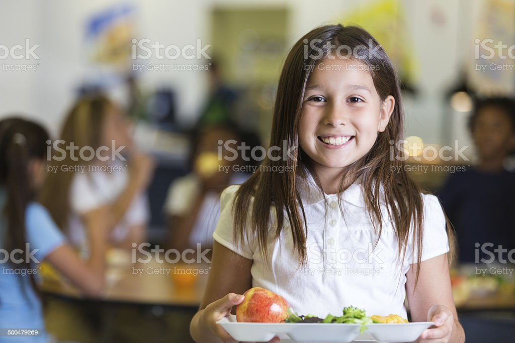 Cute Hispanic elementary school student holding tray of cafeteria food stock photo