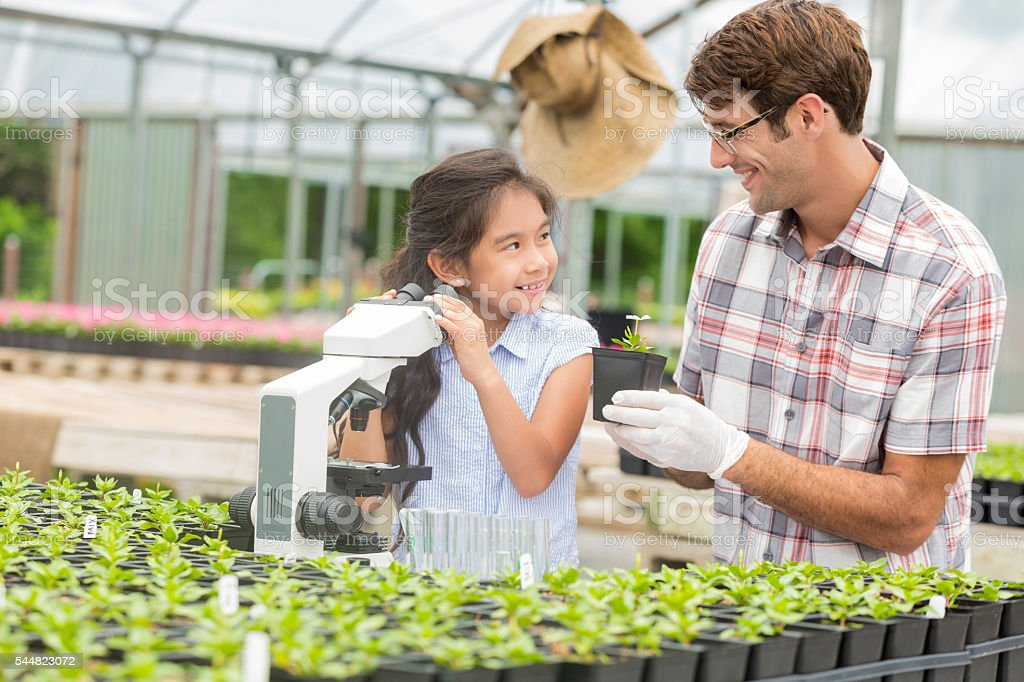 Cute hispanic girl and teacher smiling during science field trip stock photo