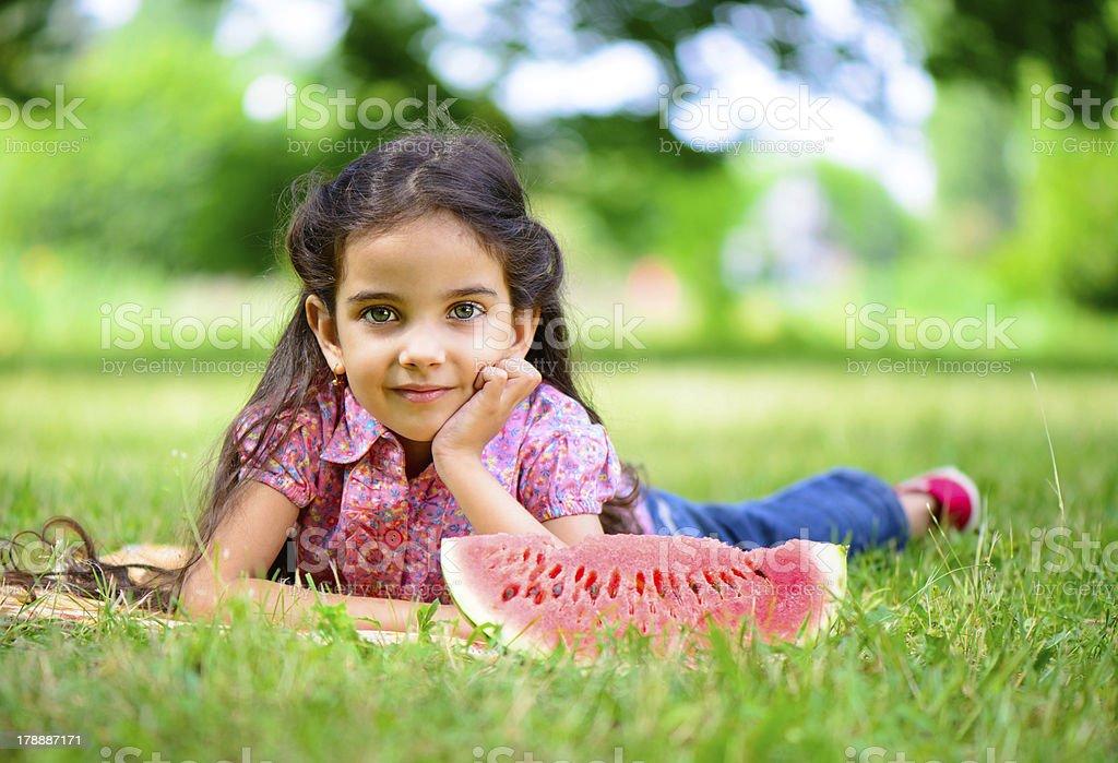Cute hispanic girl eating watermelon royalty-free stock photo