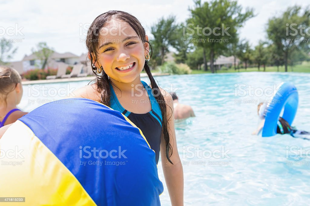 Cute Hispanic girl swimming in community pool with friends royalty-free stock photo