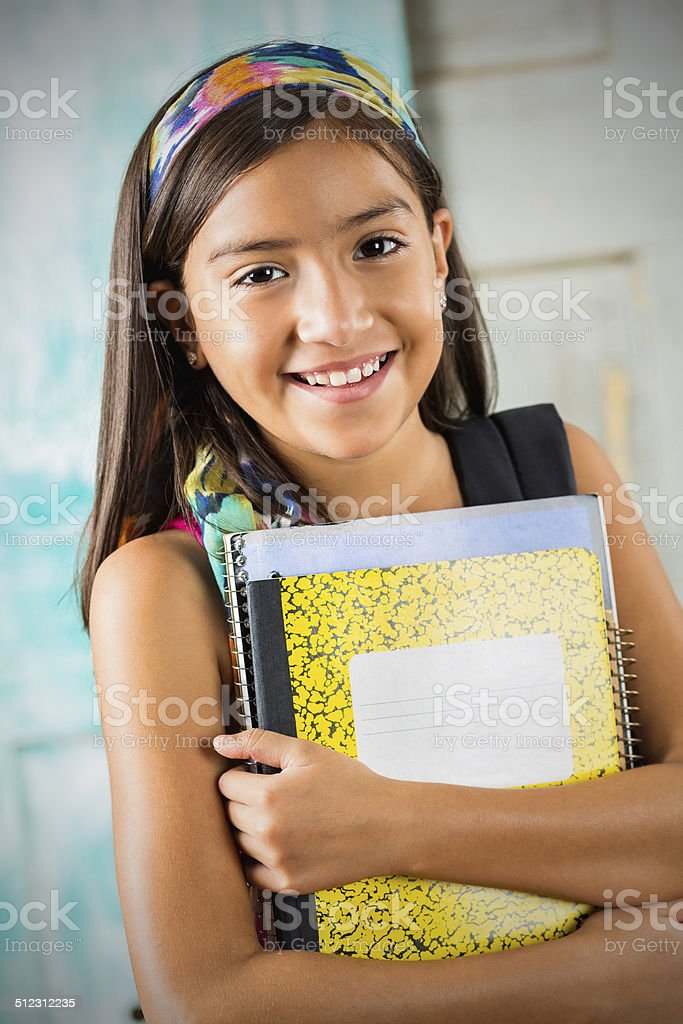 Cute Hispanic student holding books before school starts stock photo