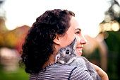 Cute Hispanic woman smiling while holding a bunny rabbit