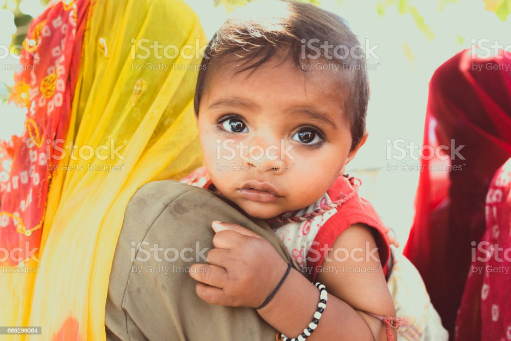 Cute little indian 7 month young baby girl, looking over mothers...