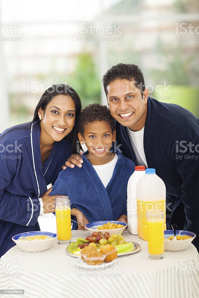 cute indian family standing behind breakfast table royalty-free stock photo