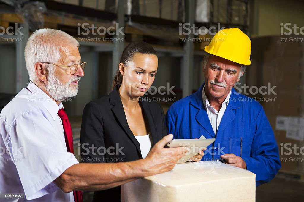 Cute inspector and two warehouse  workers checking supplies royalty-free stock photo
