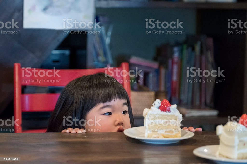 Cute Japanese Toddler Girl Looking at Birthday Cake on Table stock photo