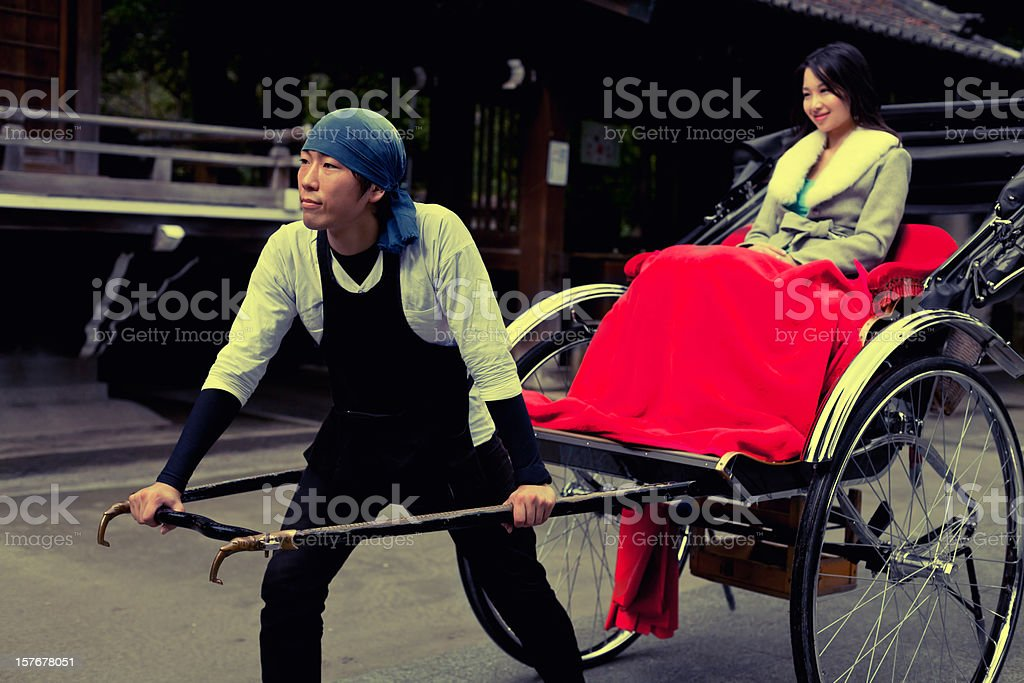 Cute Japanese woman pulled by a rickshaw stock photo