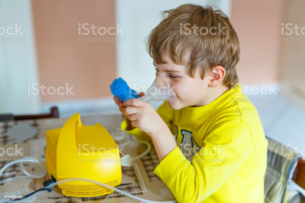 Cute kid boy making inhalation therapy by the mask of inhaler stock photo