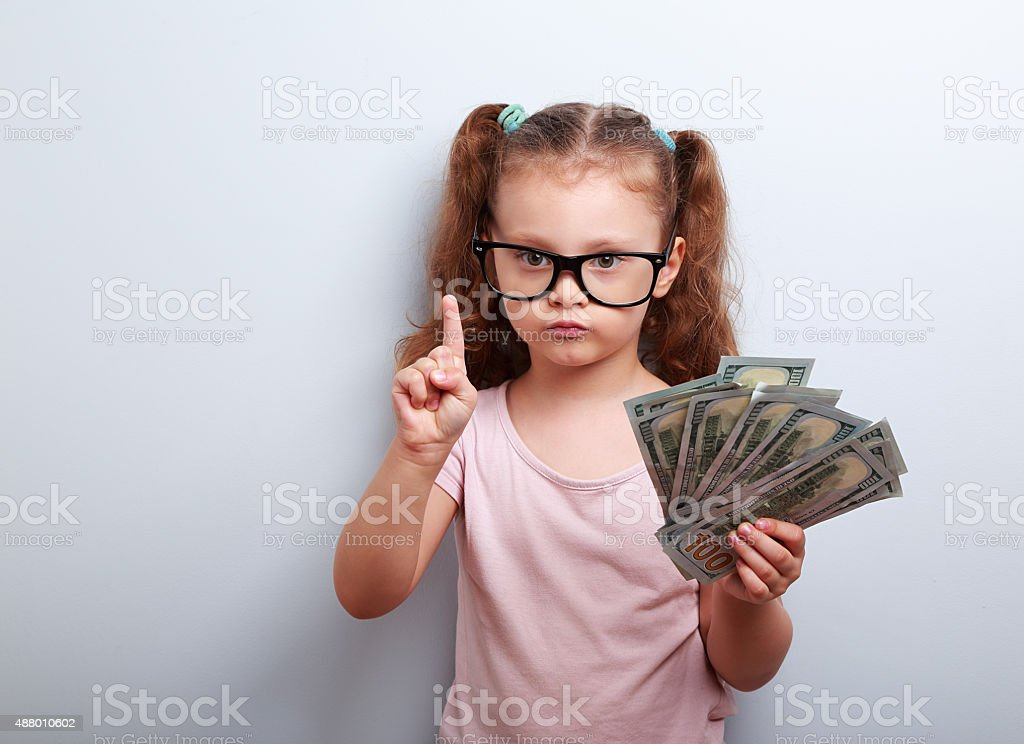 Cute kid girl holding dollars and have an idea stock photo