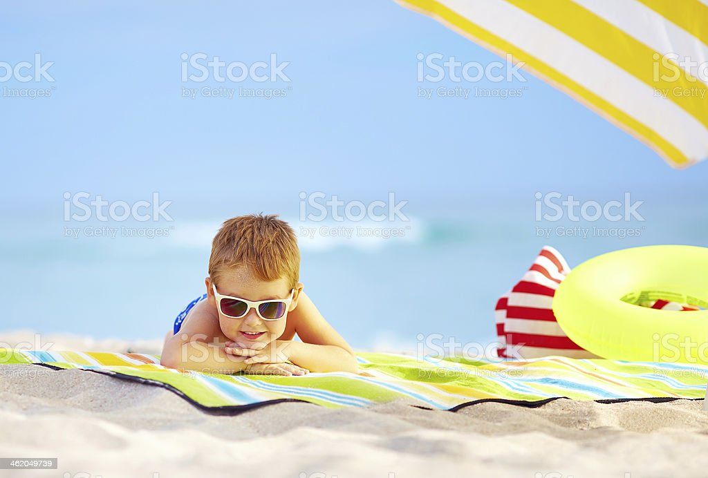 cute kid in sunglasses resting on colorful beach stock photo