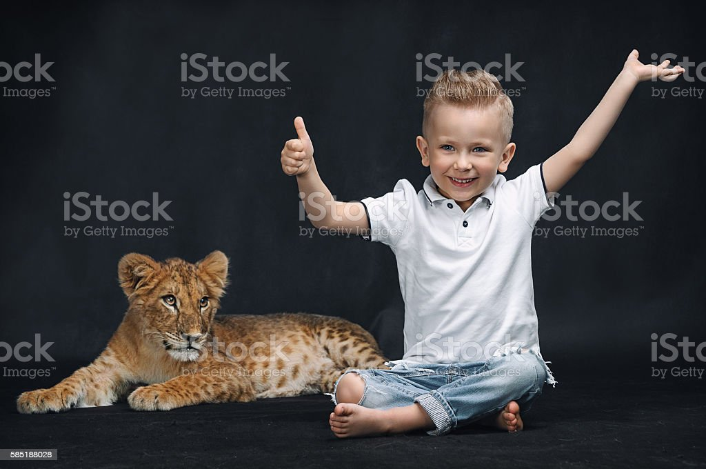 Cute kid playing with a lion cub on a black background stock photo