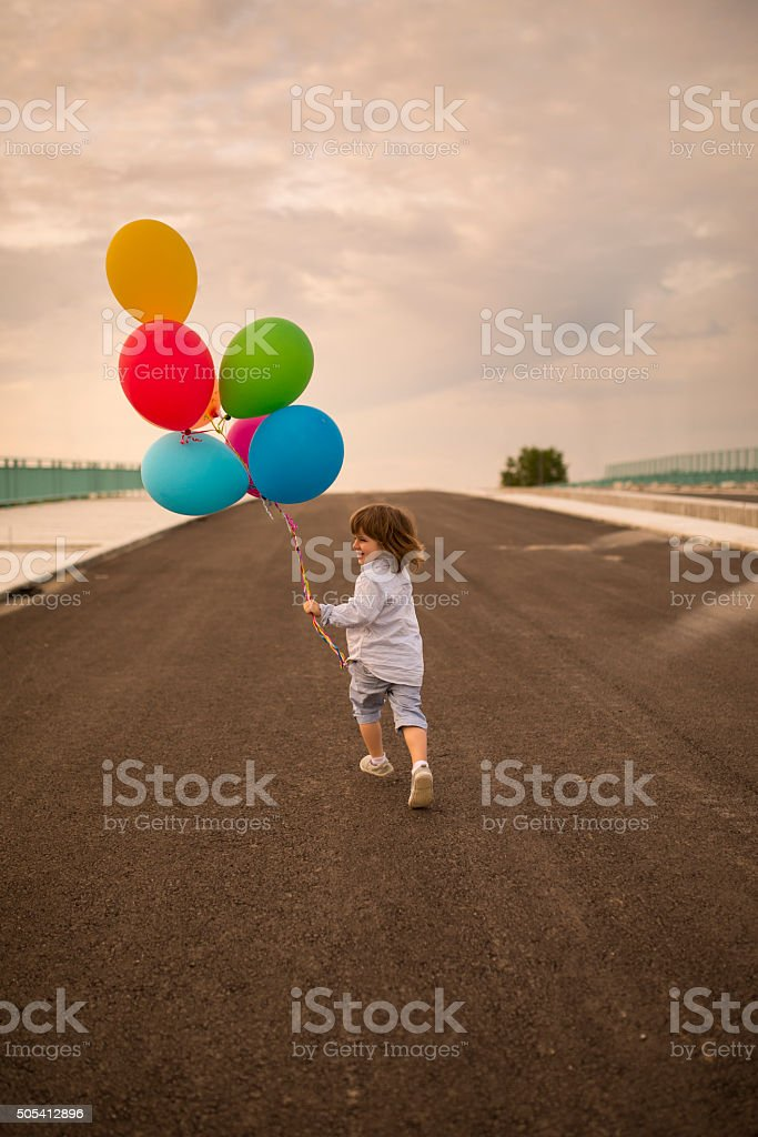 Cute kid running with colorful balloons on a bridge. stock photo