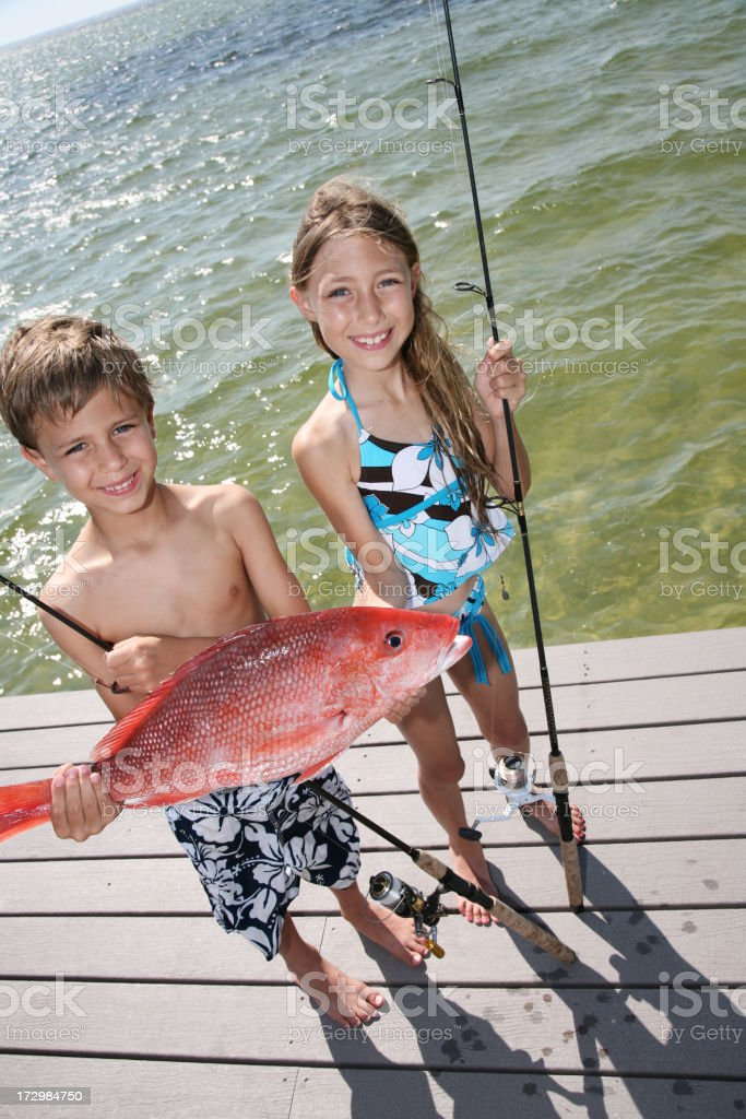 Cute kids fishing show off their red snapper catch stock photo