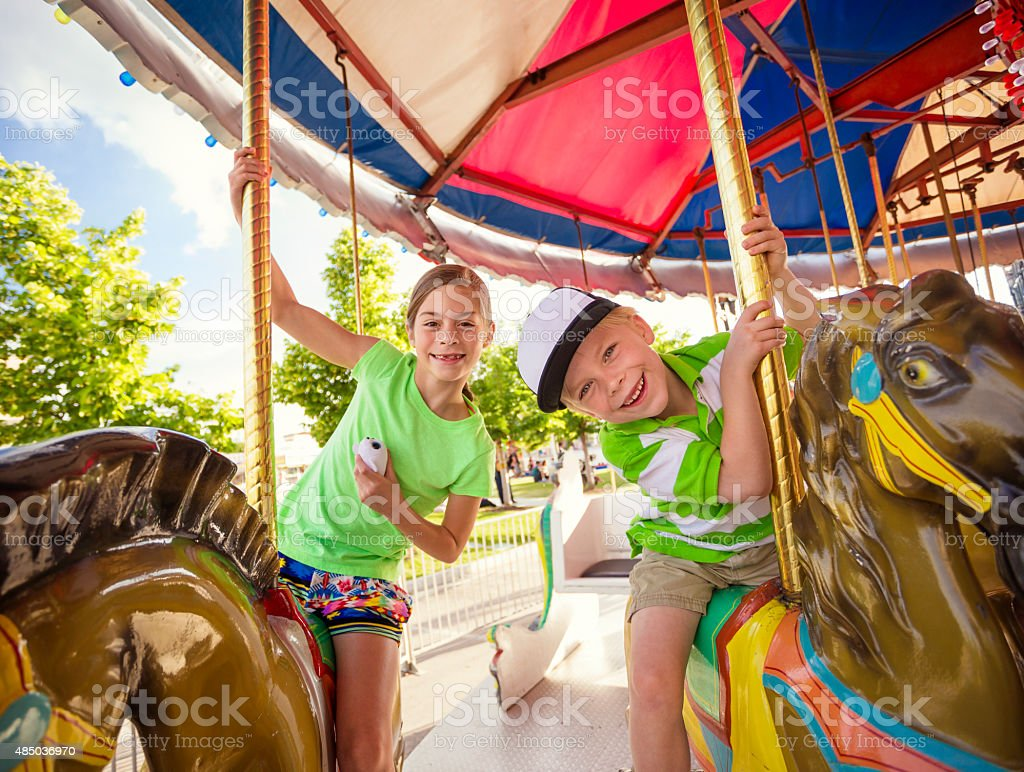 Cute kids having fun riding on a colorful carnival carousel stock photo