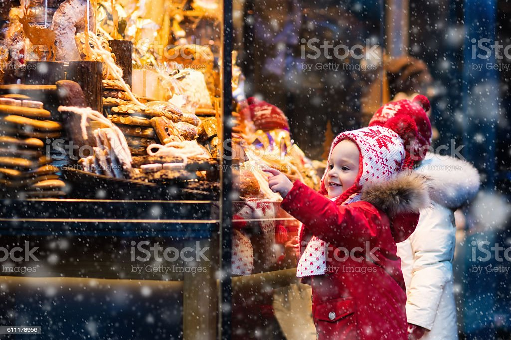Cute kids looking at candy and pastry on Christmas market stock photo