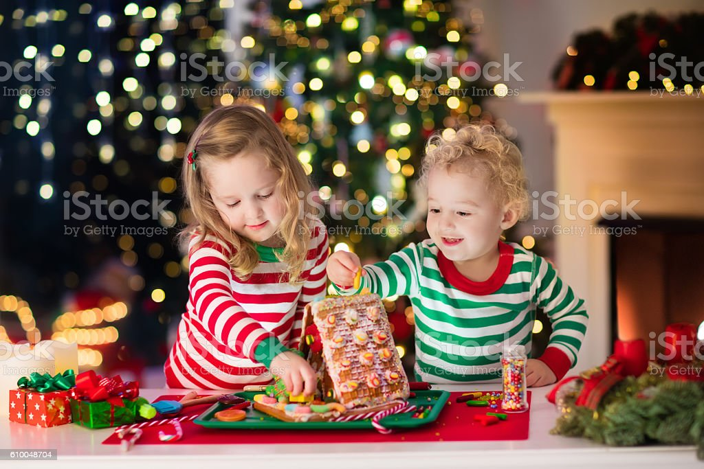 Cute kids making Christmas ginger bread house stock photo