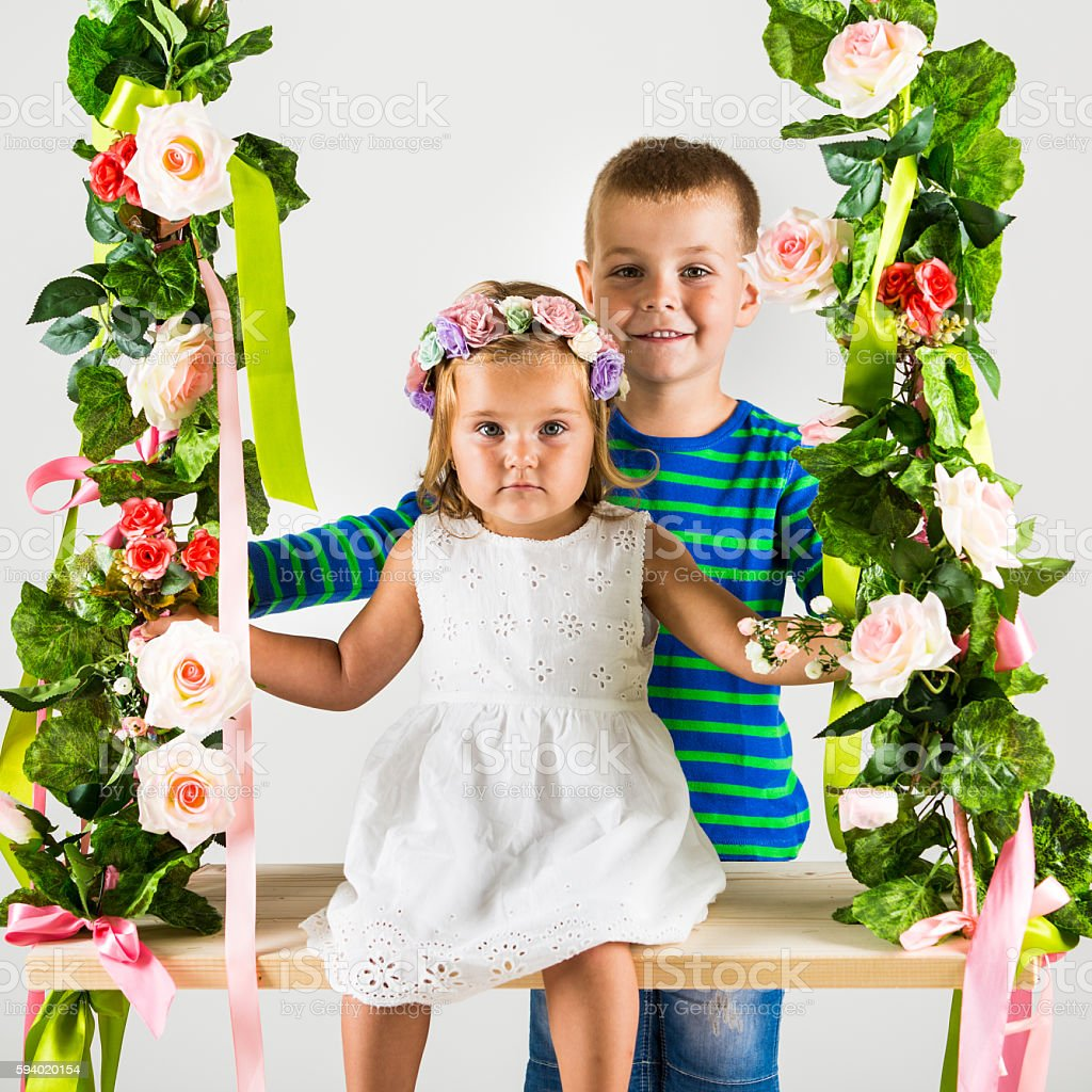 Cute kids on flower decorated swing stock photo
