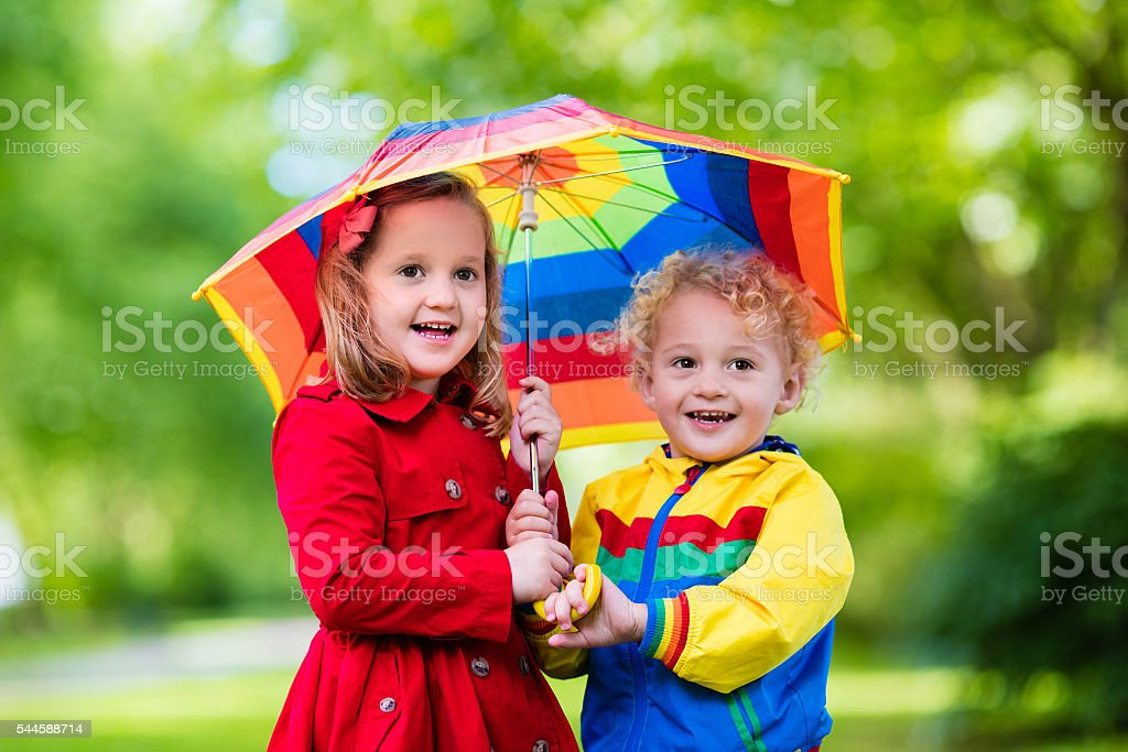 Cute kids playing in the rain under colorful umbrella stock photo