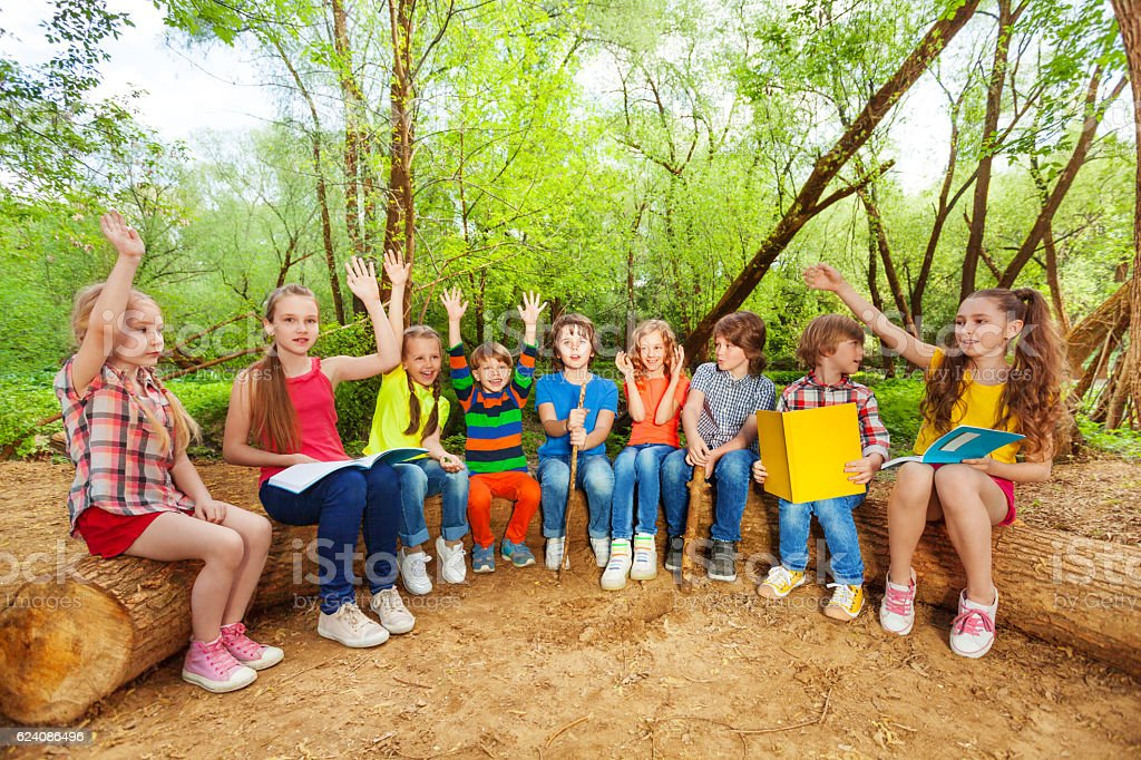Cute kids reading books outdoor sitting on the log stock photo