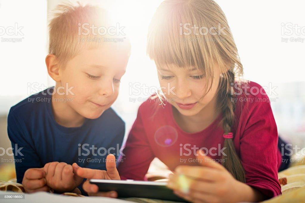 Cute kids using digital tablet stock photo