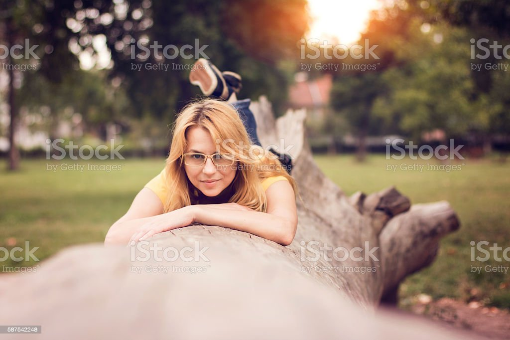 Cute lady lying on cutted tree stock photo