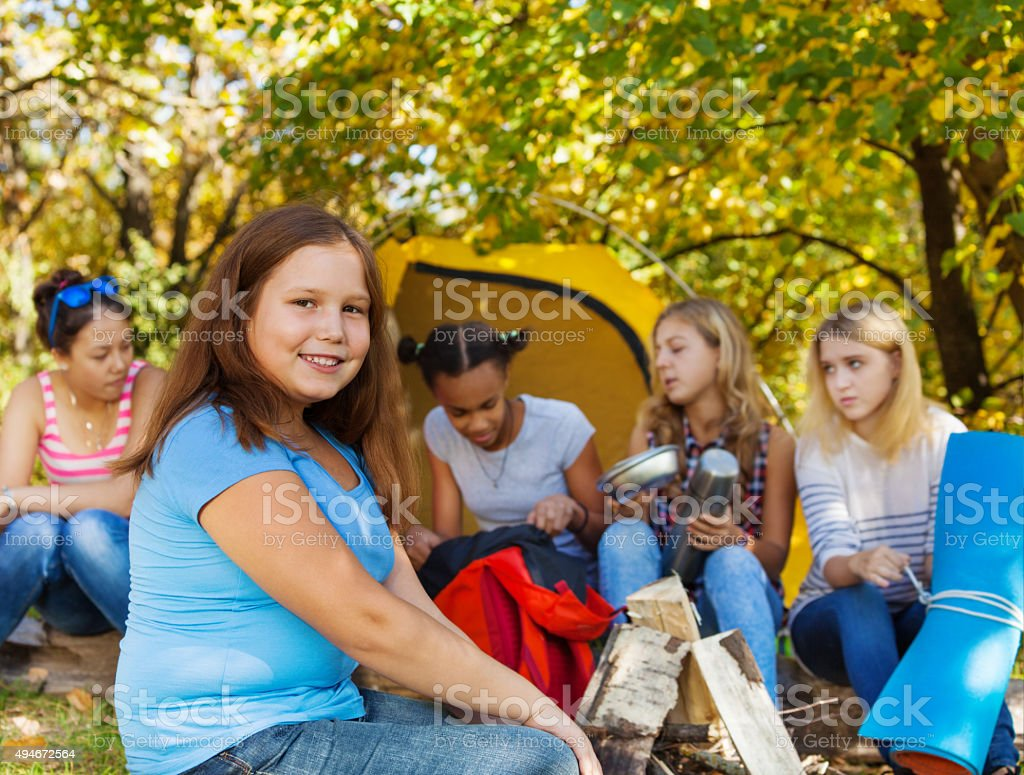 Cute large beautiful girl sitting near yellow tent stock photo