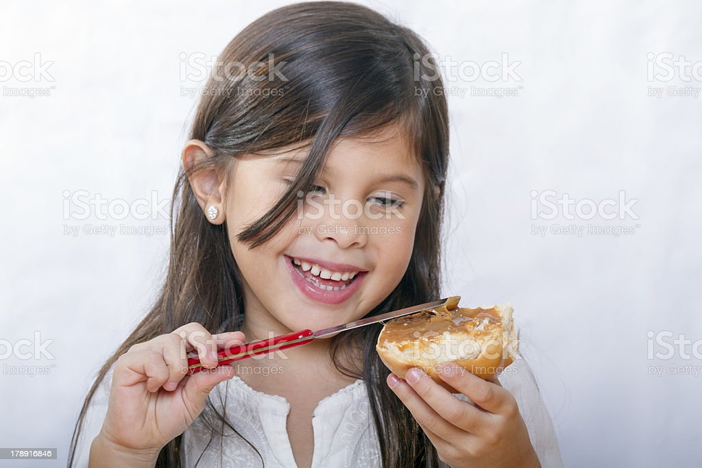 cute latina girl with long hair smiles as bread smeared stock photo