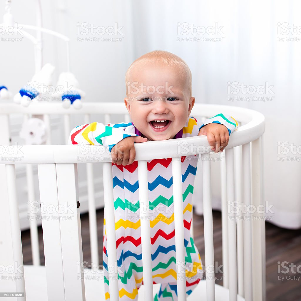 Cute laughing little boy standing in bed stock photo