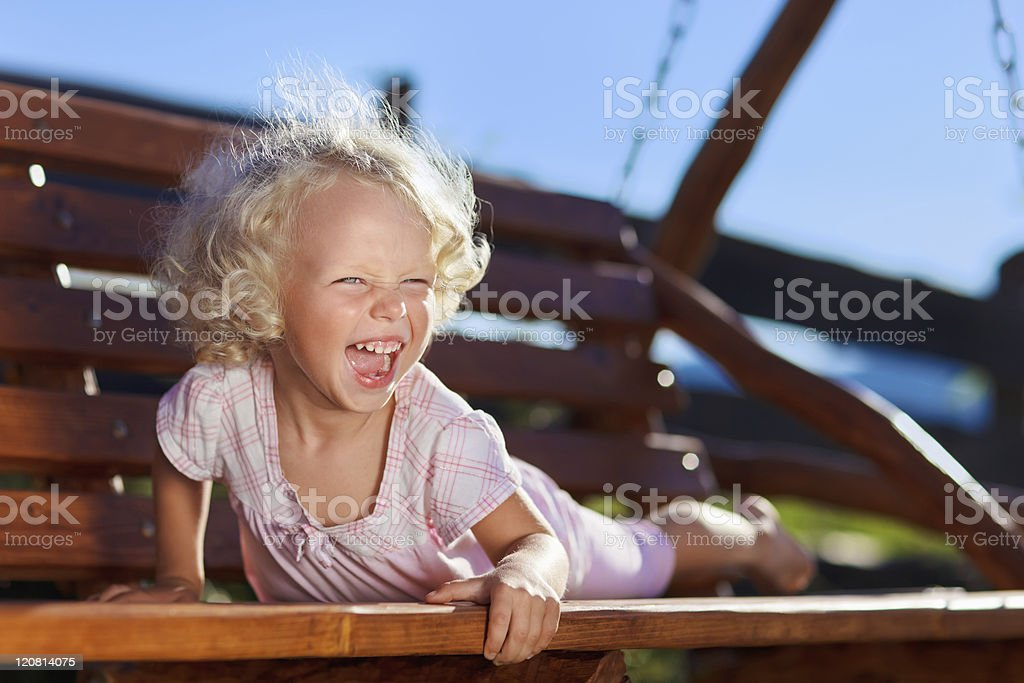 Cute laughing little girl with blond curly hair stock photo