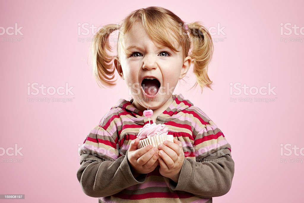 Cute litte girl dirty laughing and holding pink birthday cupcake stock photo