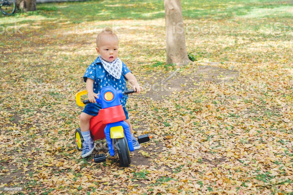Cute little Asian 1 year old toddler baby boy child riding his tricycle in summer park, kid playing toy and cycling in the garden outdoors, Child first experience concept stock photo