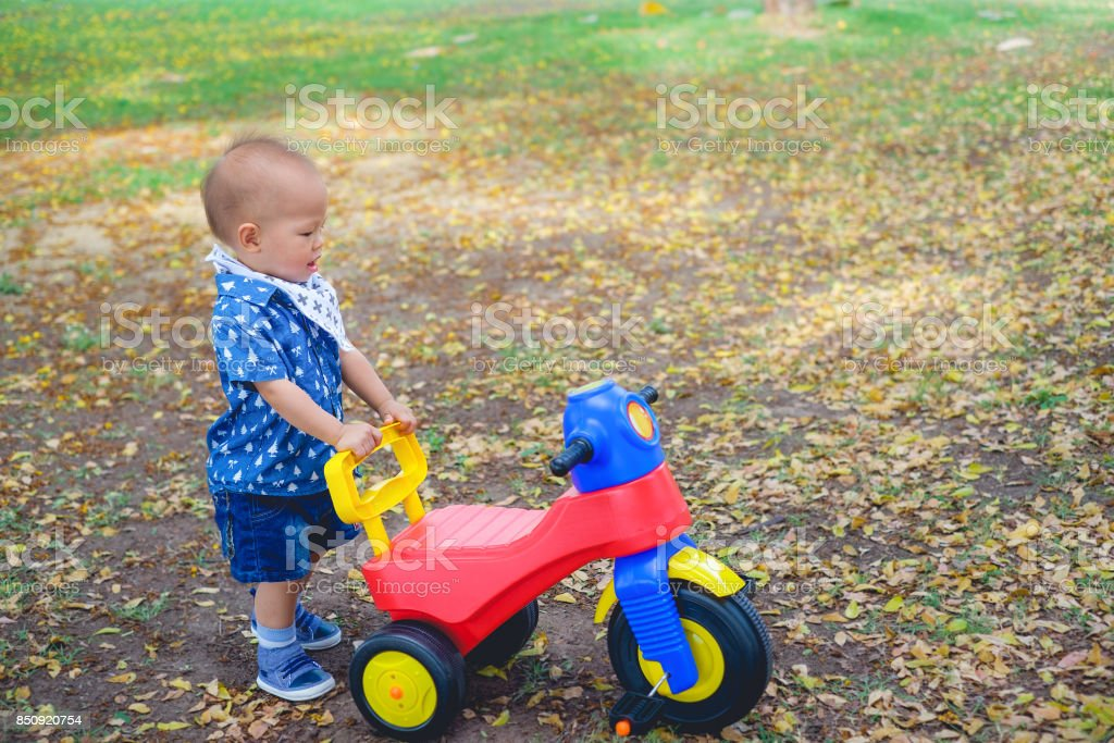 Cute little Asian 1 year old toddler baby boy child standing and playing near his tricycle in summer park, kid playing toy and cycling in the garden outdoors on nature stock photo