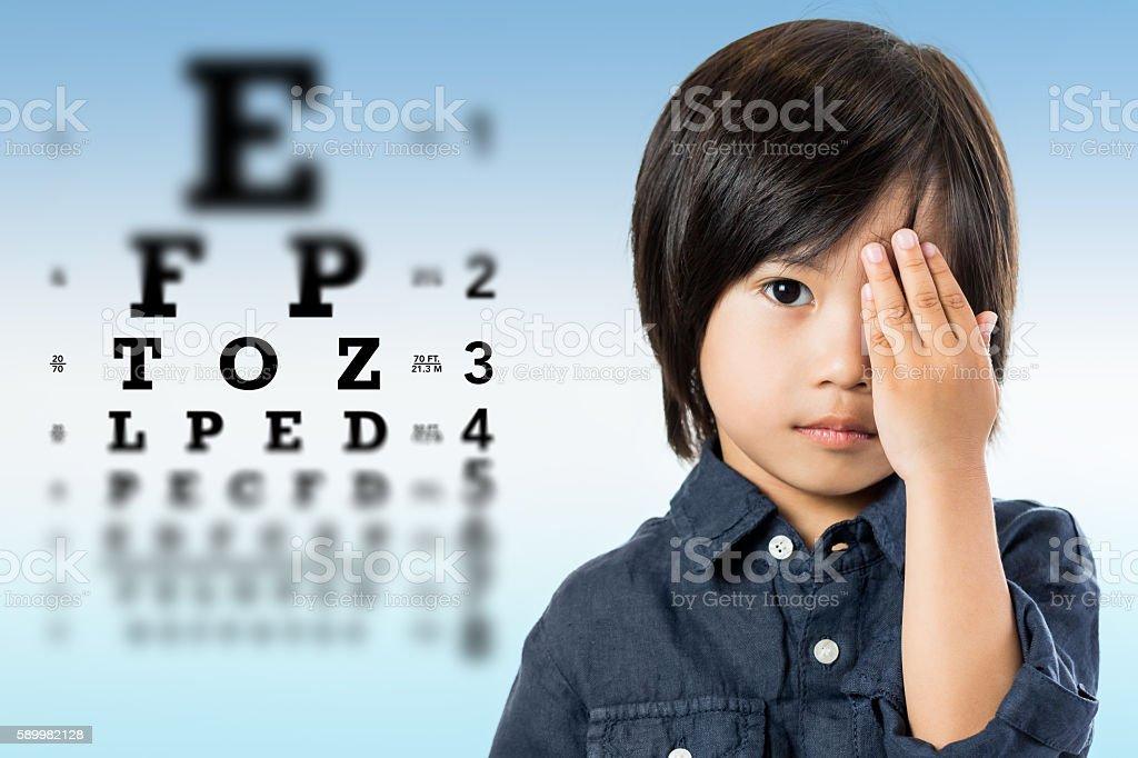 Cute little asian boy doing vision test. photo libre de droits